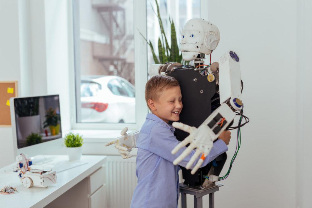 Joyful happy boy hugging a robot