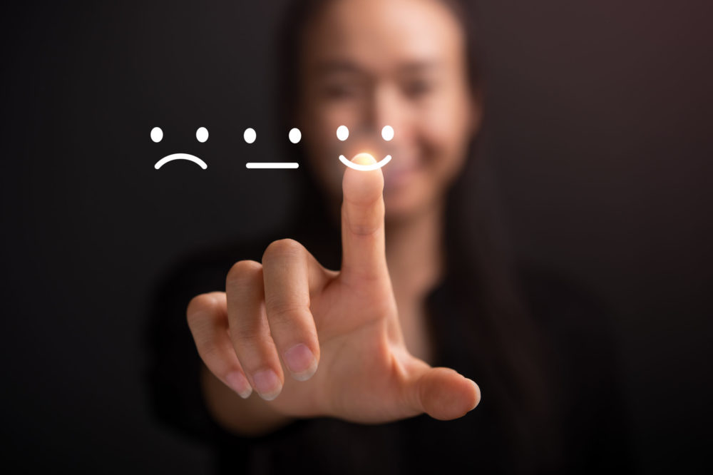 Businesswoman pressing smiley face touch screen . Business Service Satisfaction concept