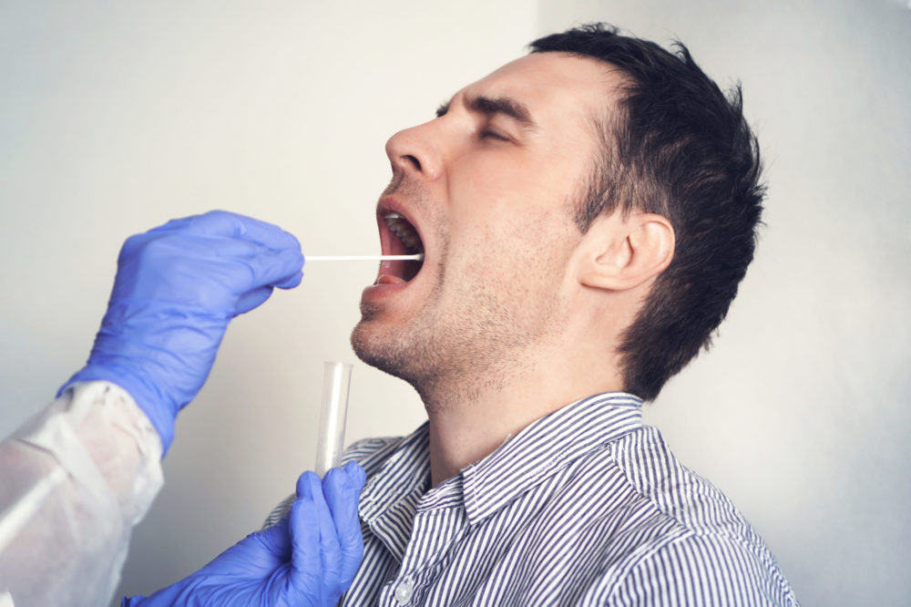 DNA test. Doctor Doing Coronavirus covid 19 Test For male Patient. Taking a saliva sample from a man. Collection of mucus from the throat for research in the laboratory.